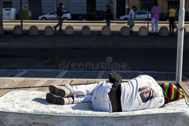 一个无家可归的黑人睡着在街道的老沙发 免版税库存图片