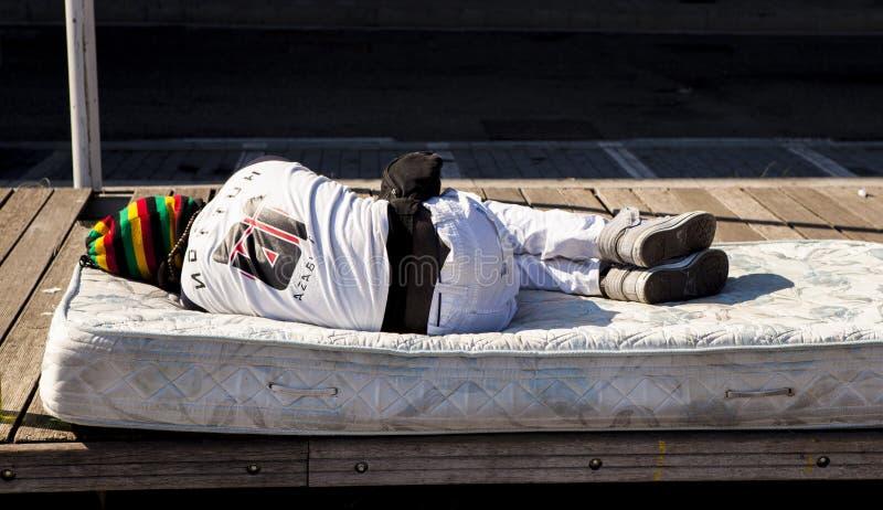 一个无家可归者在街道上睡觉 从非洲的难民热那亚,意大利街道的  图库摄影