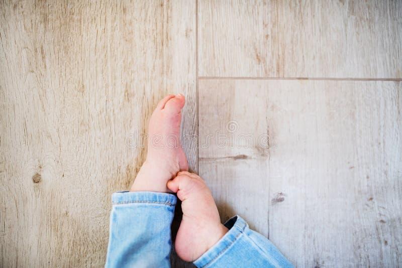 一个无法认出的男孩的婴孩脚在家坐地板 复制空间 库存照片