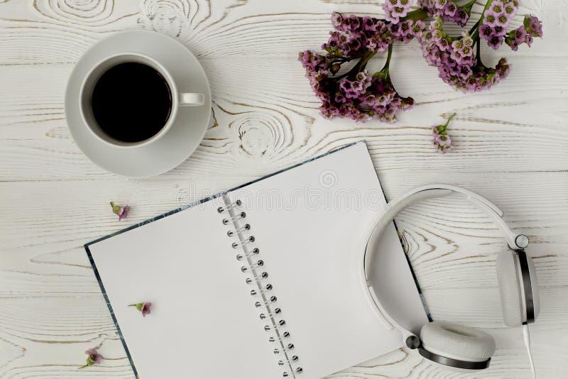 一个日志的顶视图或笔记本、耳机和咖啡和一朵紫色花在一张白色木桌上 浪漫平的设计 图库摄影