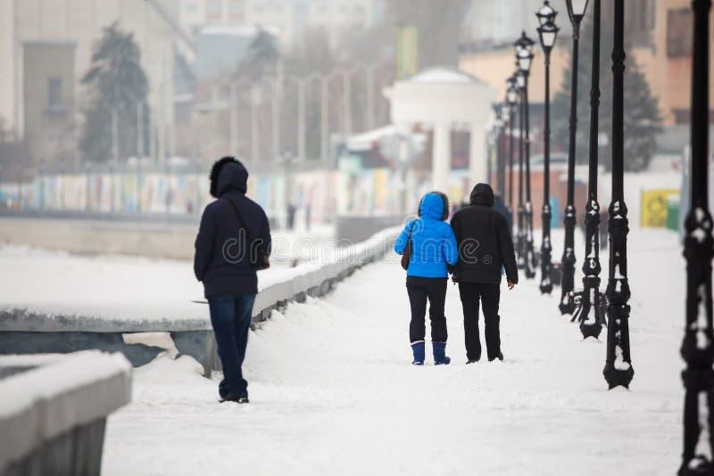 一个日期在江边的冬天 人们在街道上的雪走 在爱的一对夫妇 免版税库存图片