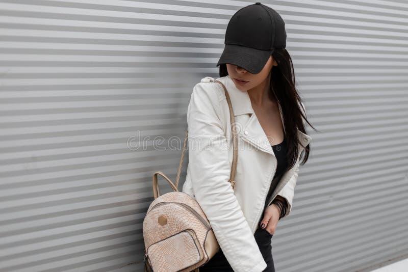 一个时兴的黑棒球帽的俏丽的现代年轻女人在牛仔裤的葡萄酒白色皮夹克有金背包的 免版税库存图片