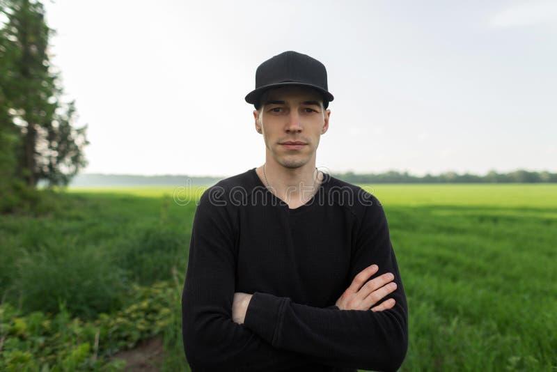 一个时兴的黑盖帽的快乐的英俊的年轻人在一件时髦的T恤杉休息在一个领域的身分在绿草中 ?? 库存图片