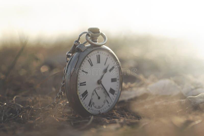 一个时钟的超现实的图象在一个神秘和神奇风景的 免版税库存照片
