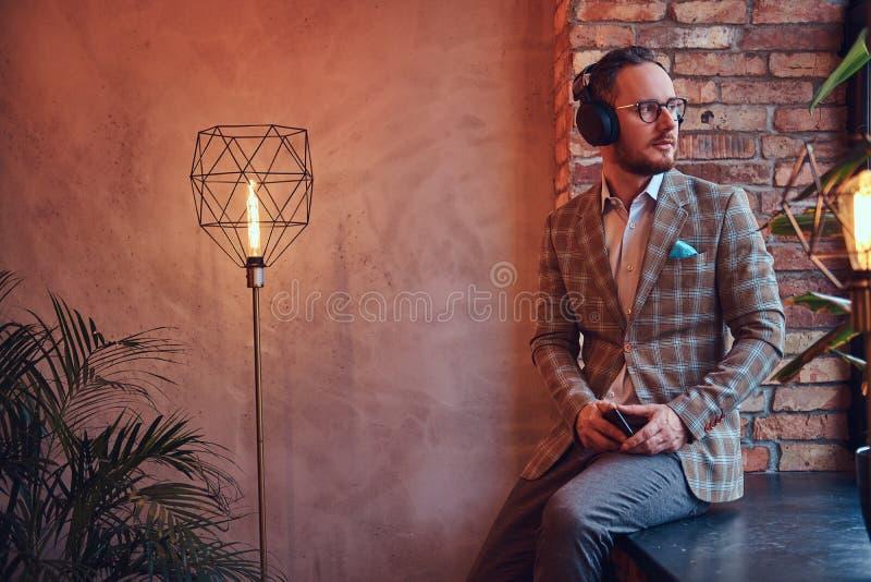 一个时髦的人和与电话和耳机的玻璃听的音乐的画象法绒衣服的坐a 库存照片