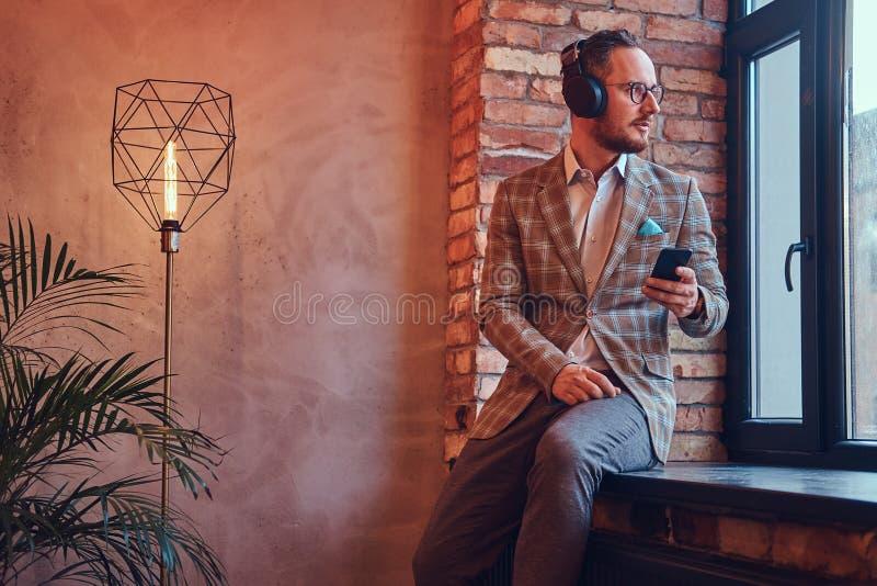 一个时髦的人和与电话和耳机的玻璃听的音乐的画象法绒衣服的坐a 图库摄影