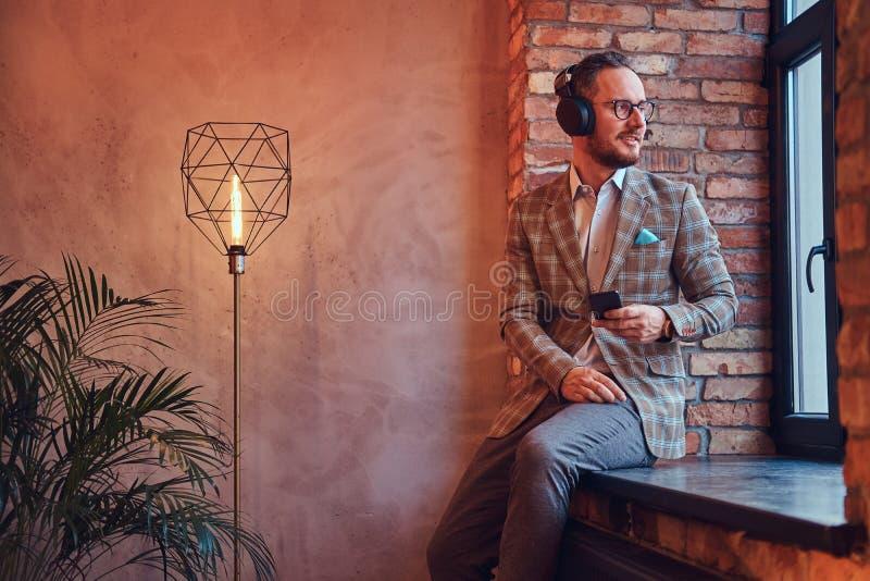 一个时髦的人和与电话和耳机的玻璃听的音乐的画象法绒衣服的坐a 库存图片