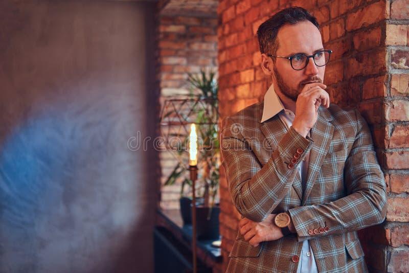 一个时髦的人的画象倾斜对一个砖墙的法绒衣服和玻璃的在有顶楼内部的一间屋子里 免版税库存图片