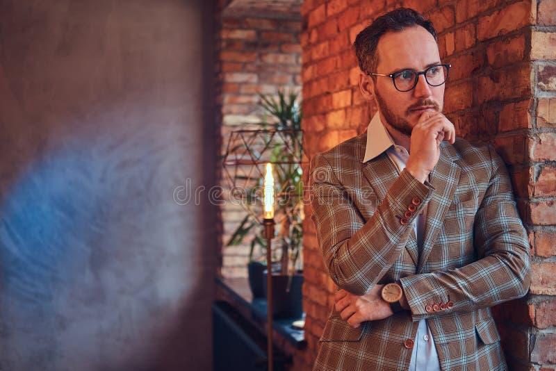 一个时髦的人的画象倾斜对一个砖墙的法绒衣服和玻璃的在有顶楼内部的一间屋子里 库存照片