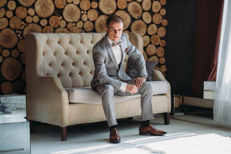 一个时髦的商人的画象一套西装的在与一件白色衬衣的灰色 一个人坐长沙发 的treadled 免版税库存照片