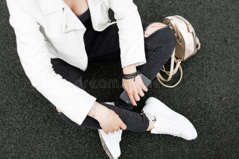 一个时髦的女人的顶视图一件白色夹克的在时髦的皮革运动鞋的被撕毁的牛仔裤有一个时髦金黄背包的 免版税库存图片