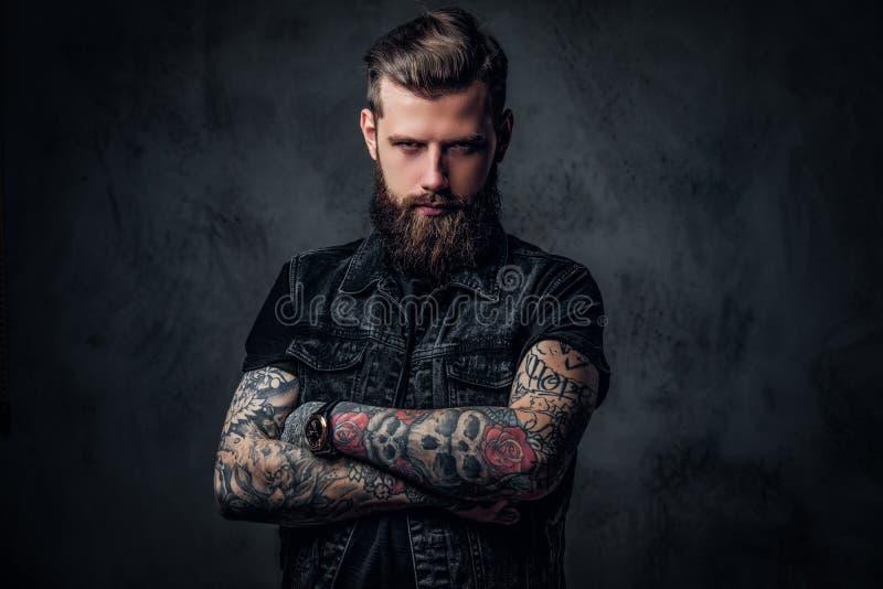 一个时髦的有胡子的人的画象用被刺字的手 演播室照片对黑暗的墙壁 免版税库存图片
