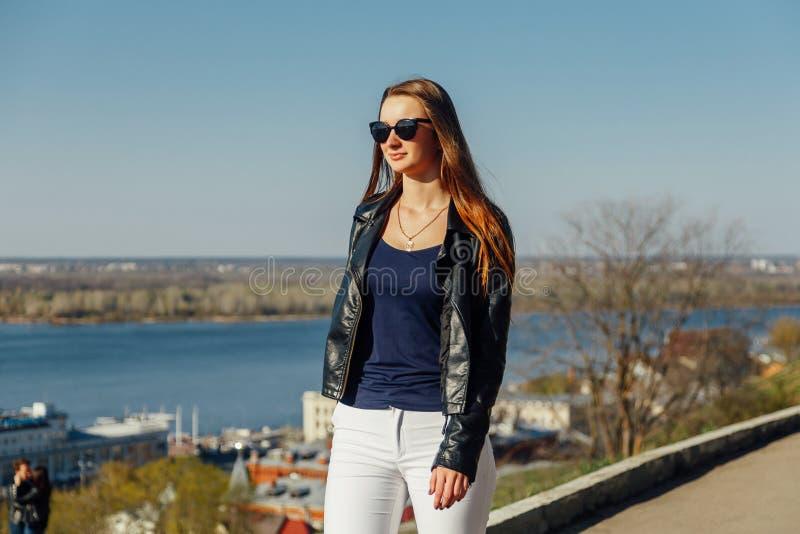 一个时髦的深色头发的女孩的画象太阳镜的,她是在皮夹克 免版税库存照片