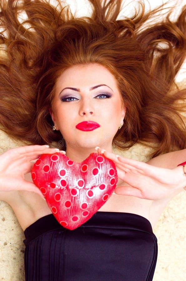 一个时兴的红发模型的画象与红色嘴唇说谎的 关闭 图库摄影