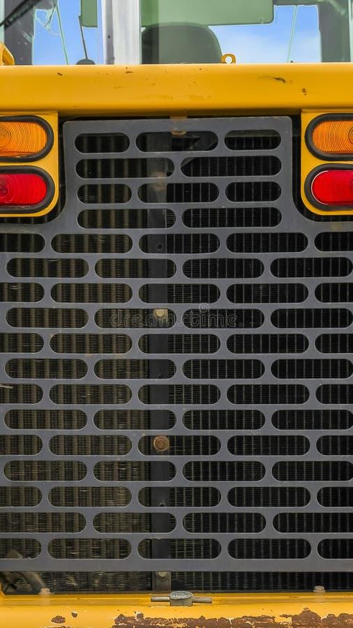 一个明亮的黄色装载者的后方的看法的垂直的框架关闭与巨大的黑轮胎的 图库摄影