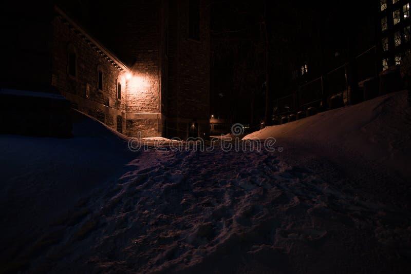一个昏暗地被点燃的鬼的胡同在一个冬天晚上在蒙特利尔,加拿大 免版税库存照片