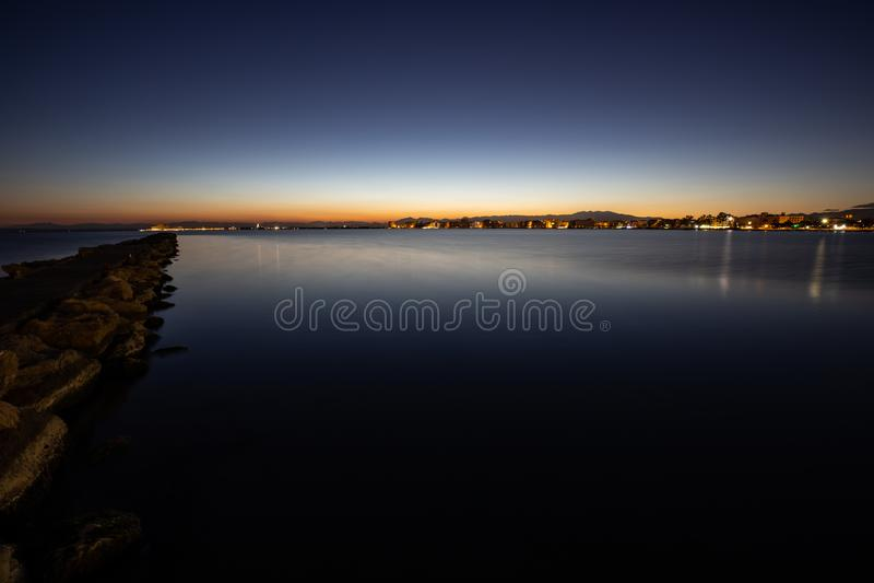 一个晚日落天空视图的长的曝光在风平浪静的 免版税库存图片