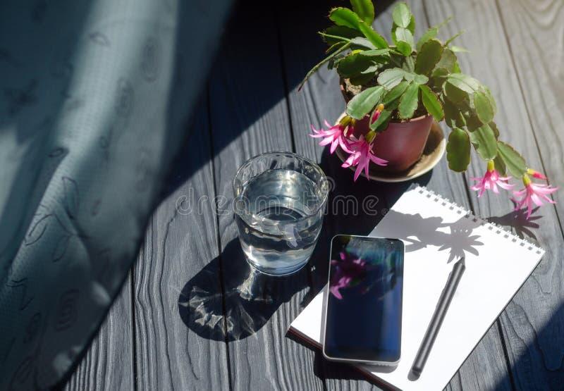 一个智能手机、笔记本有铅笔的,杯水和罐的特写镜头图象有花的在工作场所 库存图片