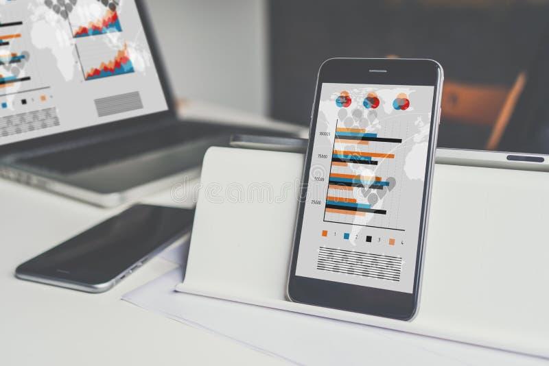 一个智能手机的特写镜头有黑屏的在一个白色桌面上的一个持有人 在背景中是被弄脏的膝上型计算机 免版税库存图片