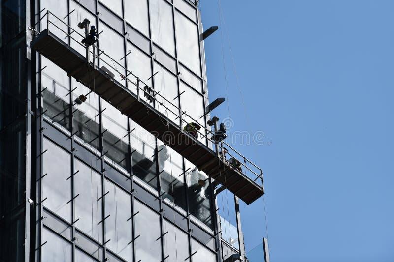 一个暂停的平台的建筑工人在摩天大楼 免版税库存照片