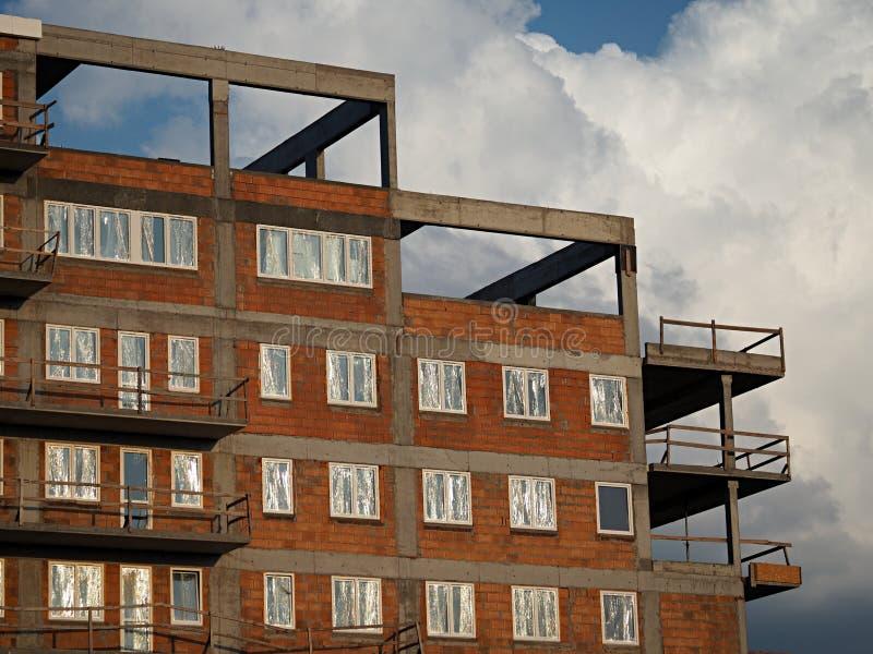 一个最近被建立的红砖住房块的顶楼与用箔和灰色具体阳台盖的塑料窗口的 免版税库存照片
