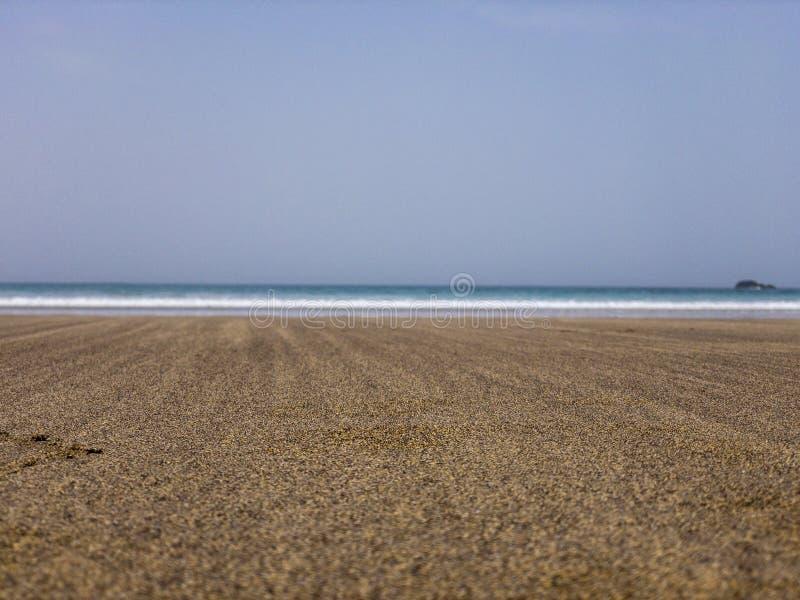 一个有波浪的海滩和海的沙粒在前景的在背景中 库存照片