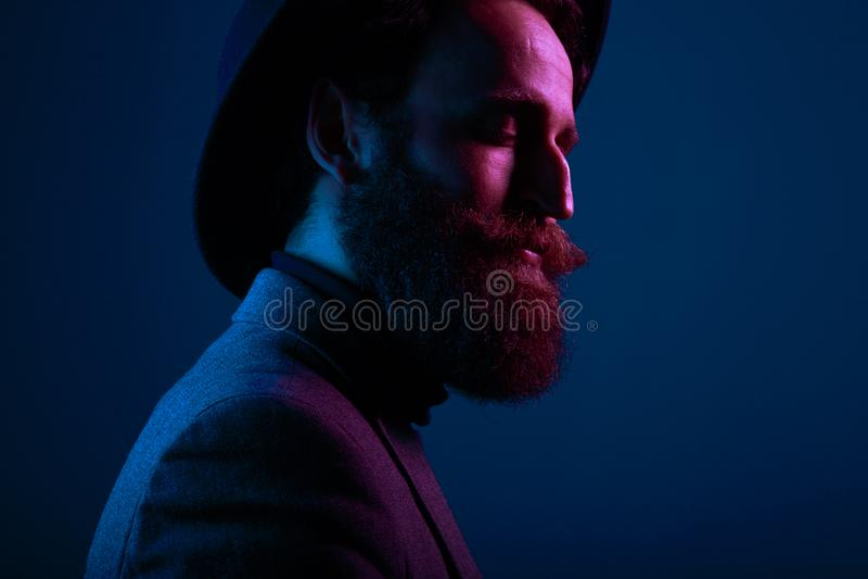 一个有胡子的人和衣服的画象帽子的,当接近的眼睛摆在外形在演播室,隔绝在蓝色背景 图库摄影