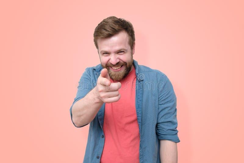 一个有胡子的人显示他的在他前面的手指和恶意地微笑嘲笑某人 隔绝在珊瑚背景 库存图片