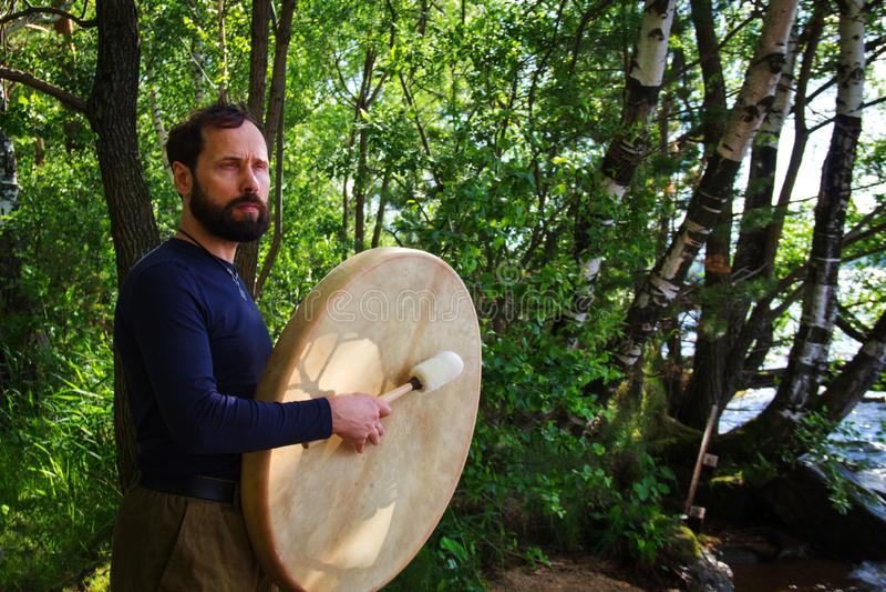 一个有胡子的人演奏在森林情感思考的生活方式的鼓 内省放松 图库摄影
