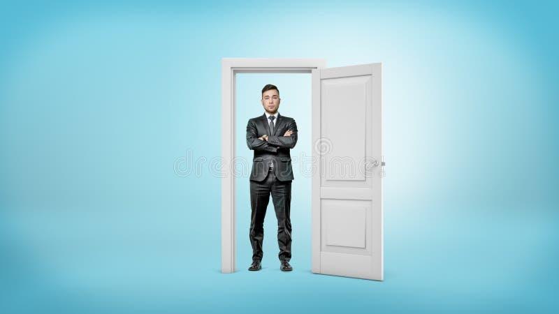 一个有胡子的商人站立与胳膊横渡在白色被删去的门框里面 免版税库存照片