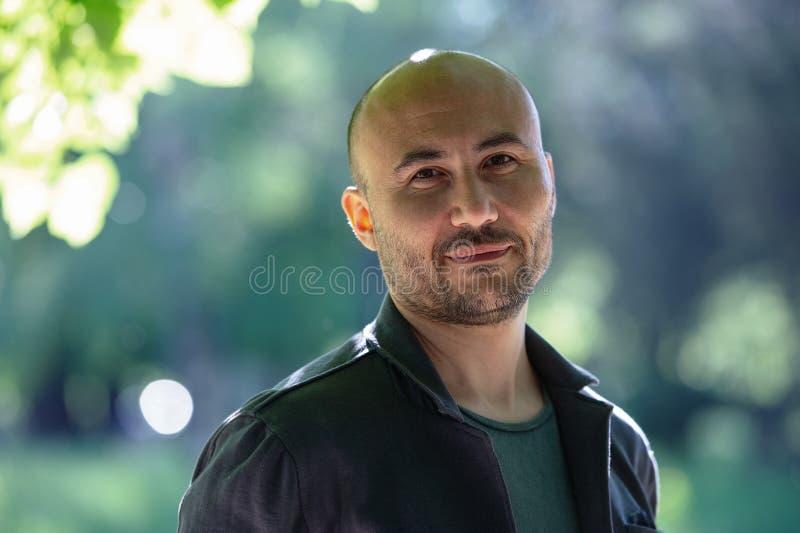一个有胡子的微笑的秃头人的面孔在公园 库存图片