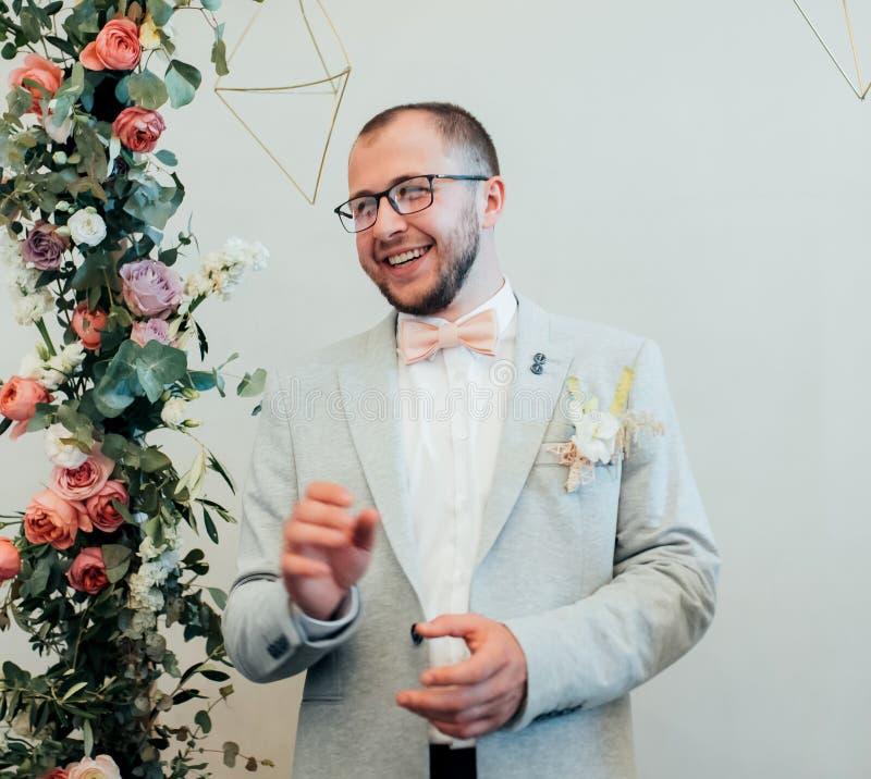 一个有胡子的新郎的情感婚礼摄影戴眼镜的在一个灰色夹克和土气样式 免版税库存照片