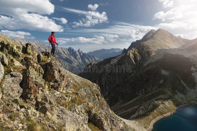 一个有胡子的旅客行家有背包的和在高峭壁的迁徙的杆立场的搬运工太阳镜和一个盖帽的 图库摄影