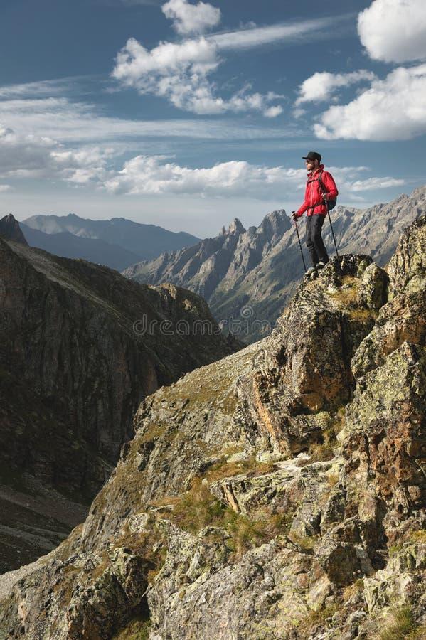 一个有胡子的旅客行家有背包的和在高峭壁的迁徙的杆立场的搬运工太阳镜和一个盖帽的 库存图片