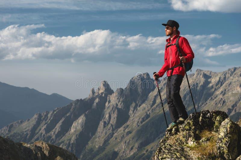 一个有胡子的旅客行家有背包的和在高峭壁的迁徙的杆立场的搬运工太阳镜和一个盖帽的 库存照片