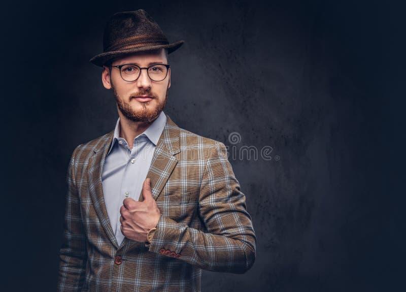 一个有胡子的行家的演播室画象帽子和玻璃佩带的 免版税库存照片