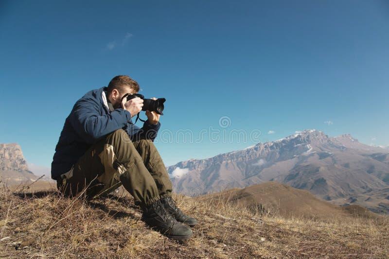 一个有胡子的行家的画象,摄影师为他的DSLR照相反对积雪覆盖的白种人背景  免版税库存图片
