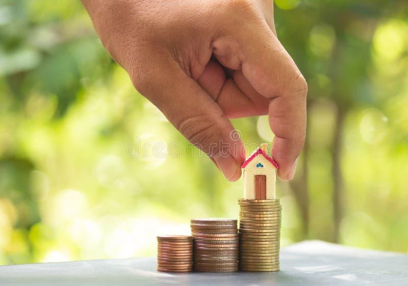 一个木家庭模型在与生长的堆硬币投入在公园的手举行,购买房子的储款金钱和贷款 免版税库存照片
