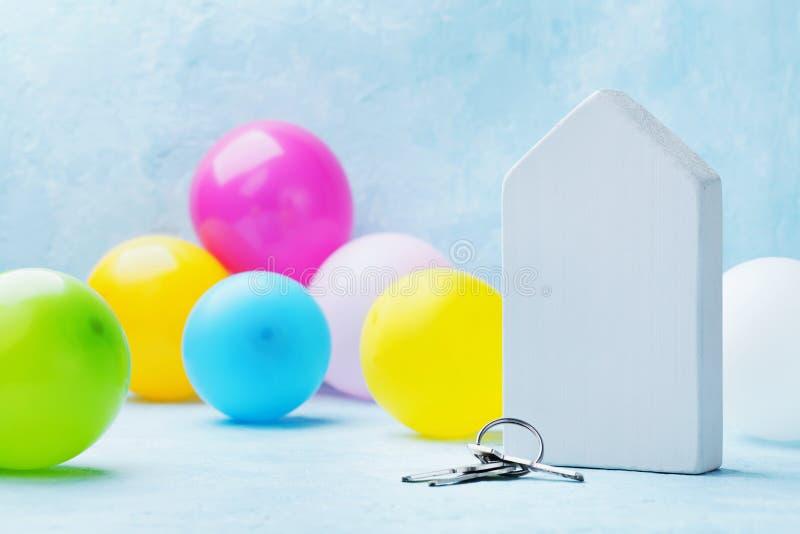一个木房子的模型有钥匙串的和五颜六色的气球在轻的背景 乔迁庆宴,移动,房地产 图库摄影