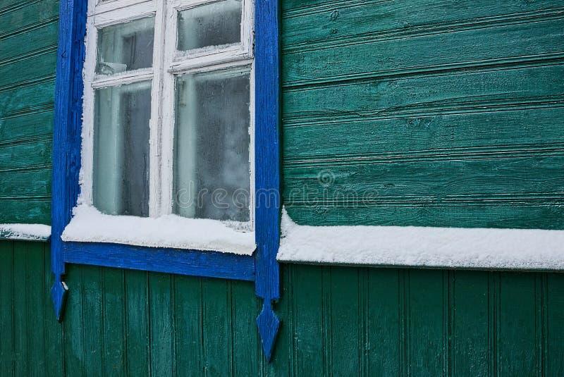 一个木房子的绿色墙壁有窗口和白色雪的 免版税库存照片