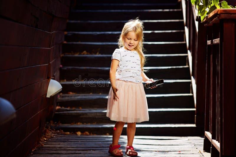 一个木楼梯的金发碧眼的女人享受暑假的 免版税库存图片