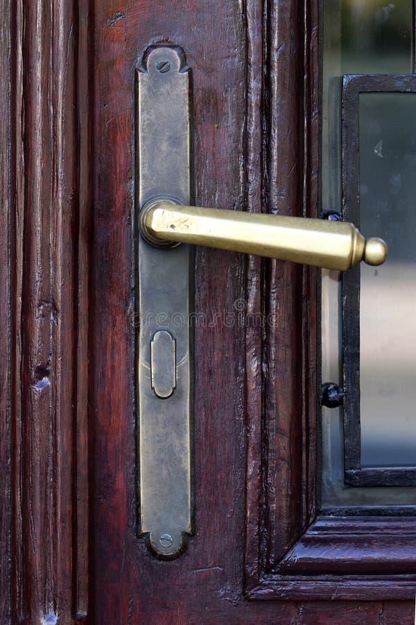 一个木门的老黄铜把柄 免版税库存图片