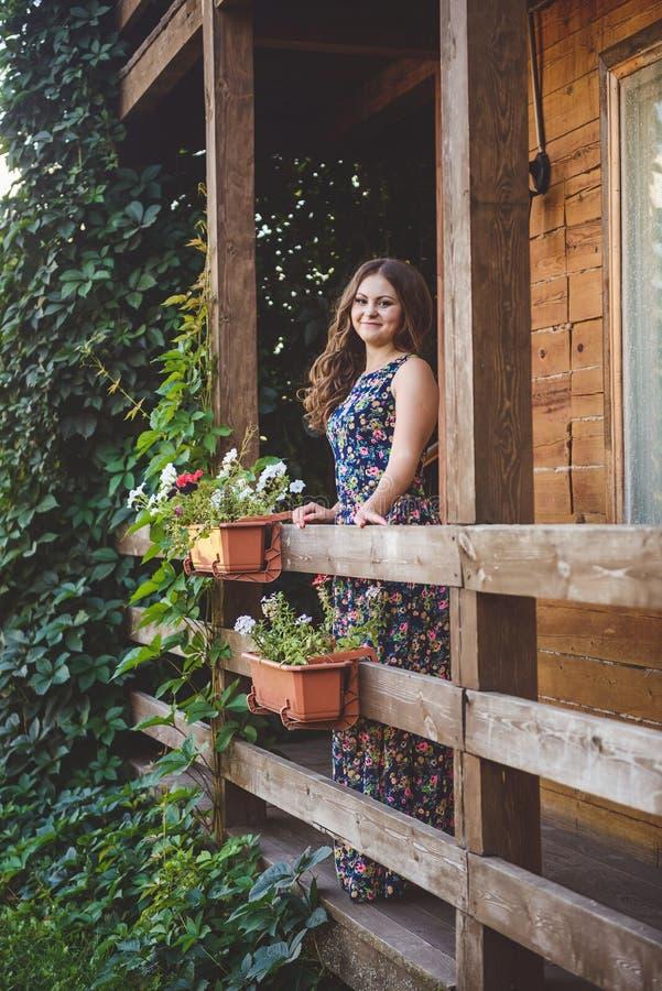 一个木阳台的年轻美丽的妇女,握在栏杆的手 在她的自然和花附近 免版税库存图片