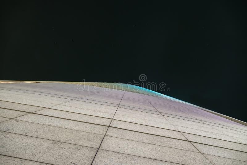 一个未来派摩天大楼的门面在夜之前 免版税库存照片