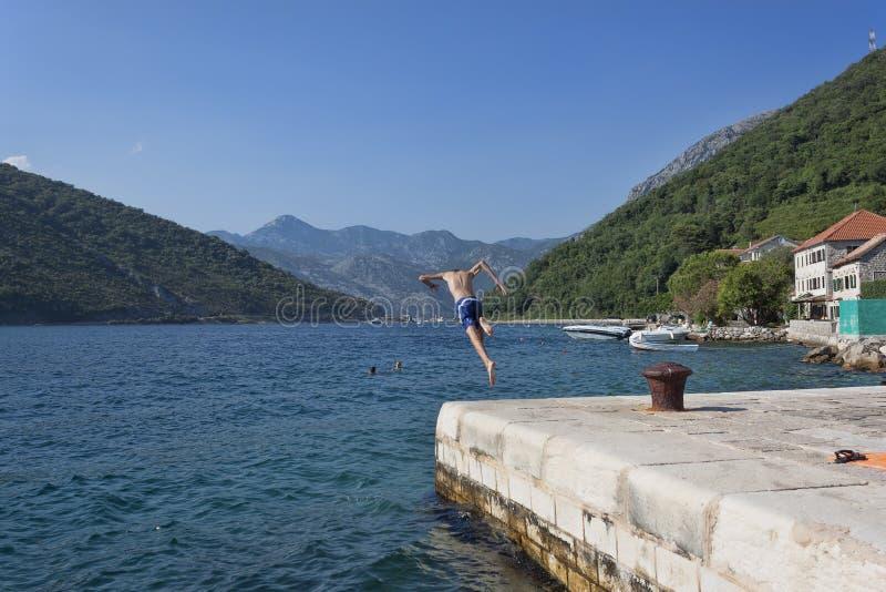 一个未知的年轻人跳进从码头的水在v附近 免版税库存照片