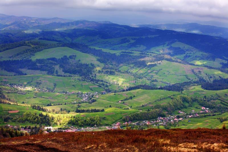 以一个村庄为背景的一个美好的山风景谷和步行的对山 库存图片