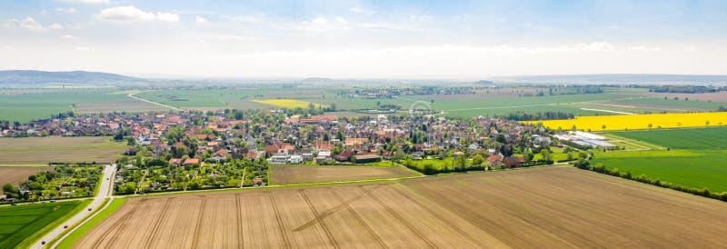 一个村庄的空中照片综合全景在有房子的德国北部在与领域的一个文化风景之间和 免版税图库摄影