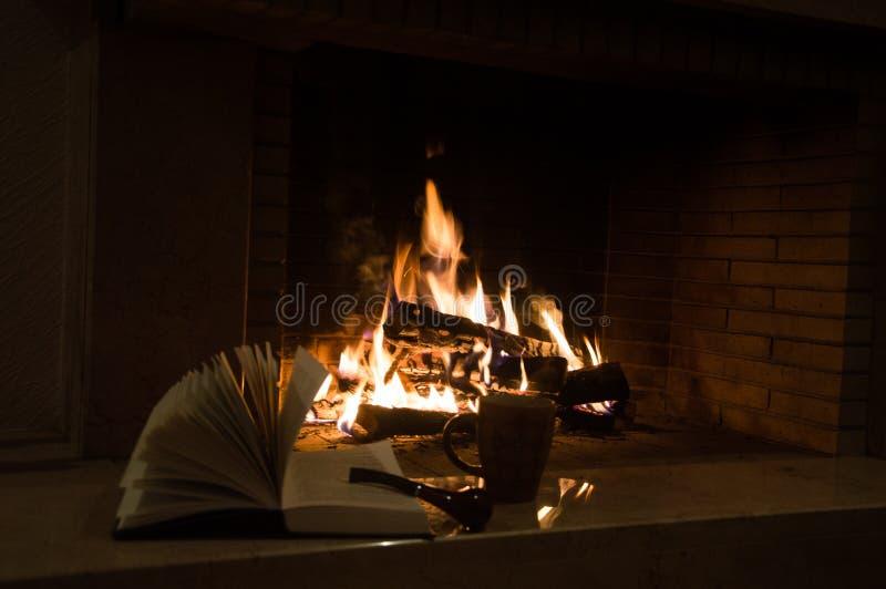 一个杯子、一本开放书和一只烟斗在壁炉附近 库存图片