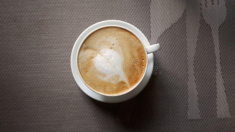 一个杯子与叶子装饰的热奶咖啡 库存图片
