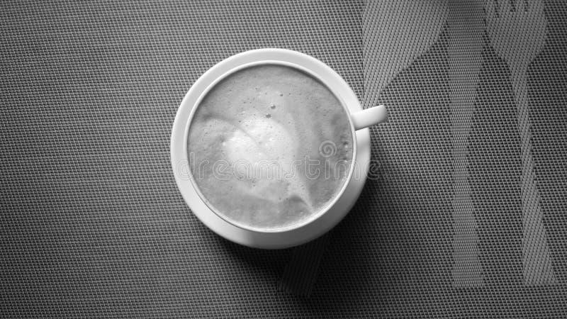 一个杯子与叶子装饰的热奶咖啡 库存照片